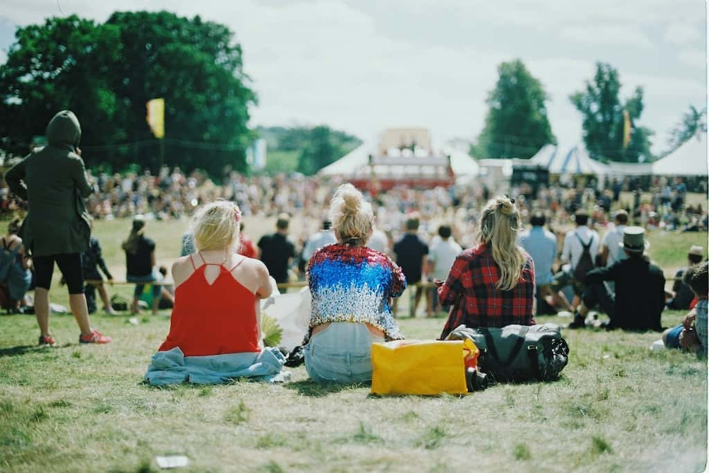 potential audience, three girls sitting on a grass watching concert