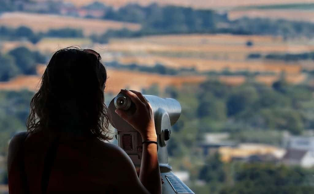 woman holding a telescope pointing at beautiful view