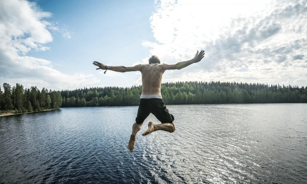 man jumping into a Lake