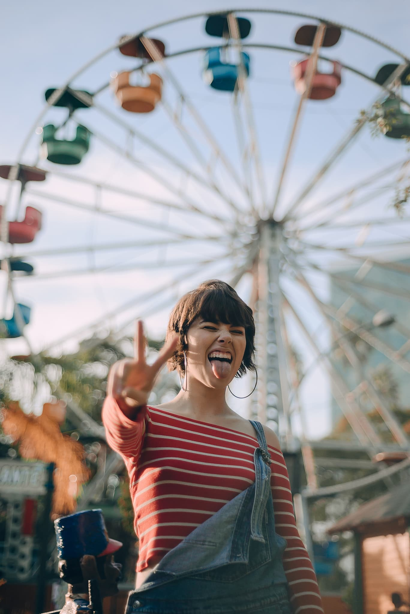 girl in front of a colourful Ferris wheel