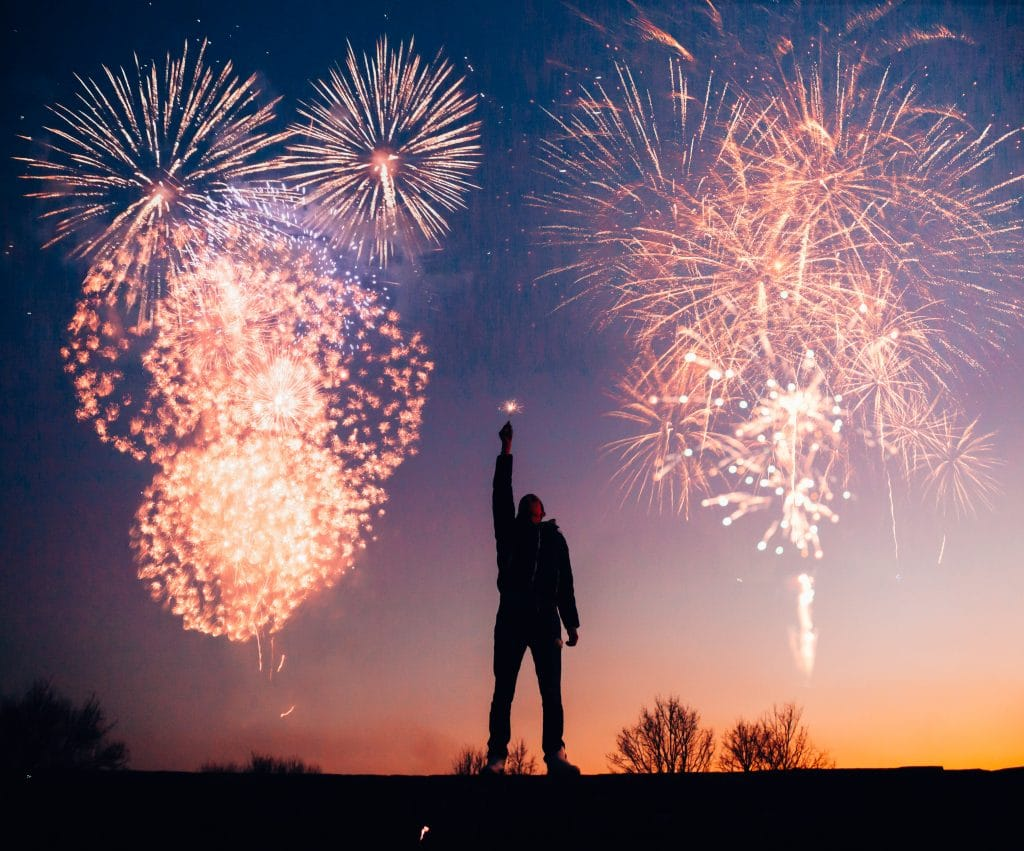 man with fireworks in the background