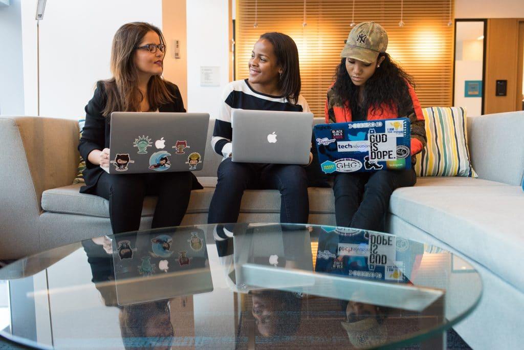 three women with laptops