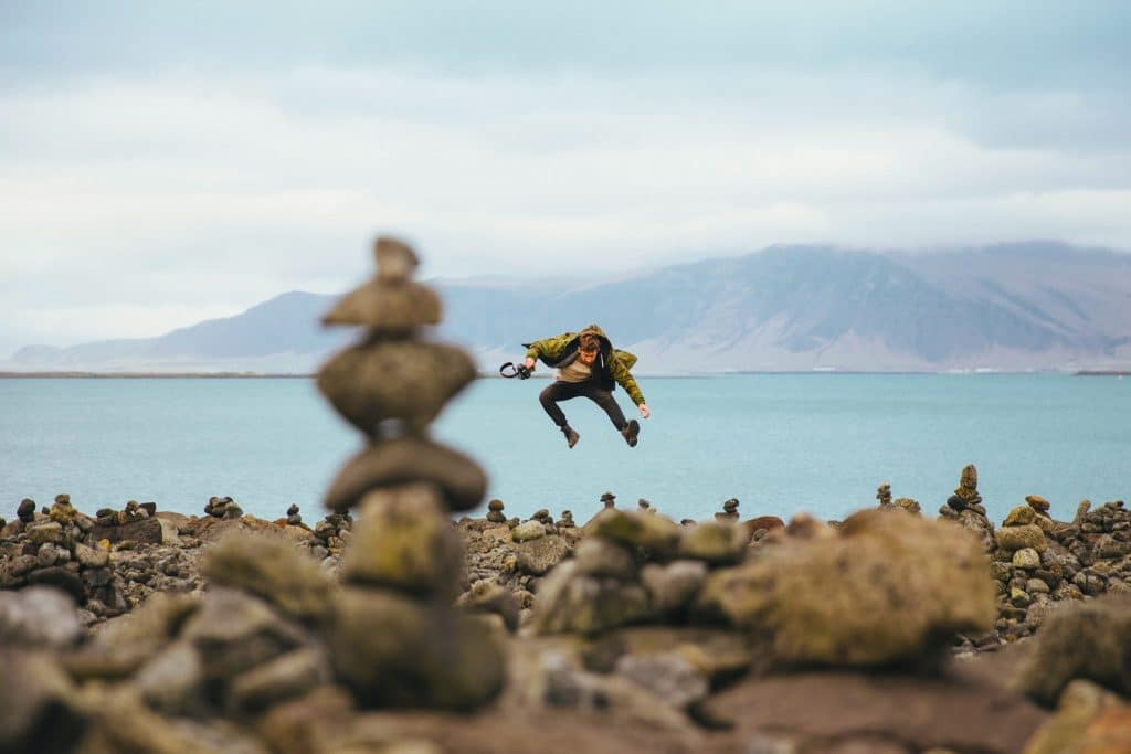 A young caucasian hiker jumping on a stoney shore