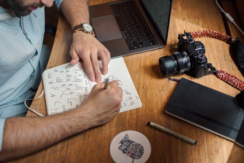 man drawing design on paper