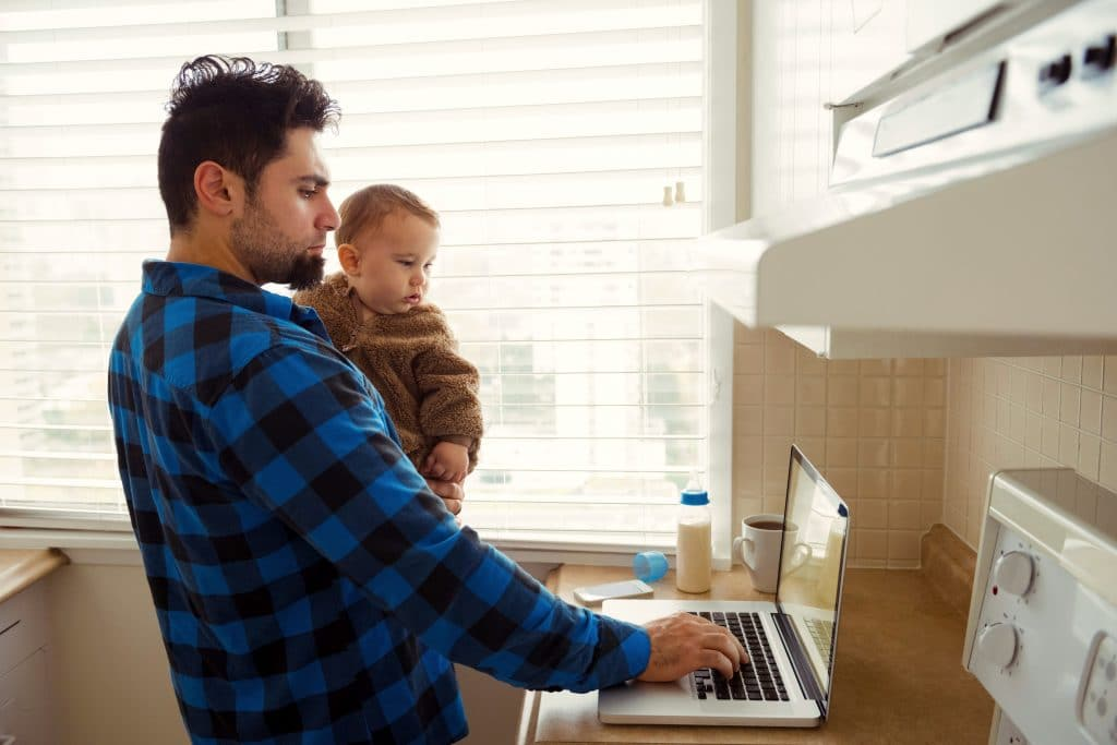 man holding a child looking at computer