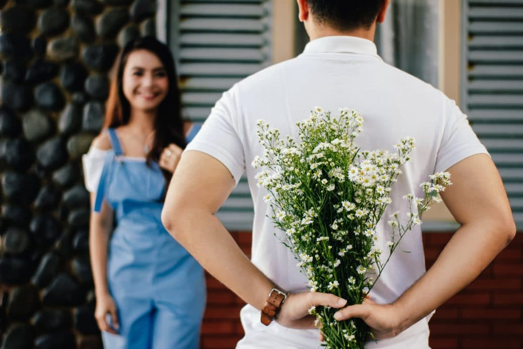 man giving flowers to a woman