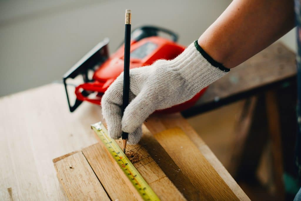 person measuring a wood board