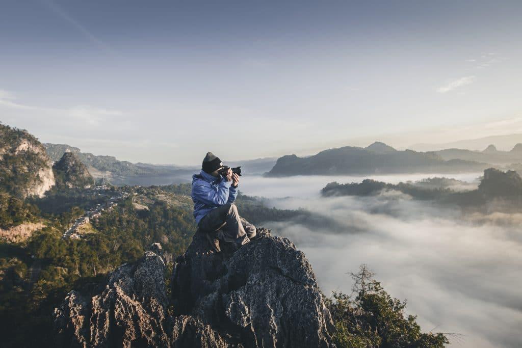 man sitting on mountaintop